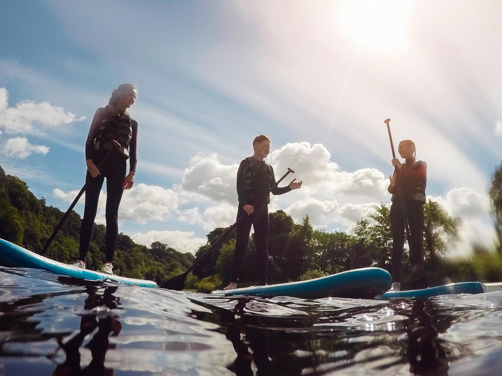 Stand-up paddleboarding group on lake