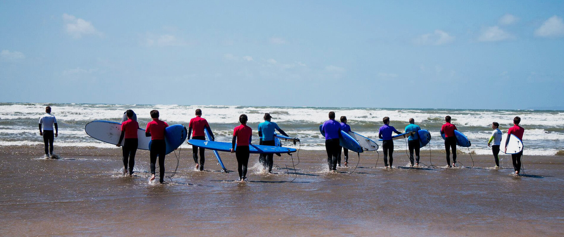 Surfers walking out to start their lesson